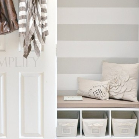 Closet With White Door Open And Blue And White Striped Accent Wall Inside, Bench, Pillows, And Baskets Underneath